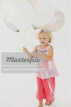 Girl holding balloons Stock Photo - Premium Royalty-Free, Image code: 6108-05865591