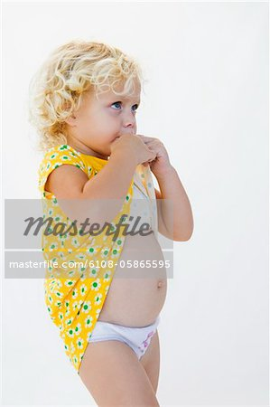 Girl biting her dress Stock Photo - Premium Royalty-Free, Image code: 6108-05865595