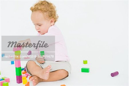 Baby boy playing with blocks Stock Photo - Premium Royalty-Free, Image code: 6108-05865678