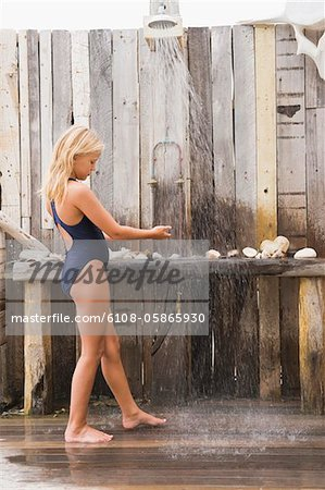 Girl under a beach shower Stock Photo - Premium Royalty-Free, Image code: 6108-05865930