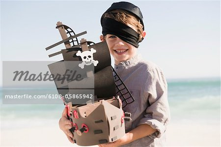 Boy in pirate costume playing with a toy boat Stock Photo - Premium Royalty-Free, Image code: 6108-05865942