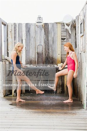 Two girls under a beach shower Stock Photo - Premium Royalty-Free, Image code: 6108-05865948