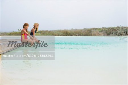 Two girls sitting on a platform at an infinity pool Stock Photo - Premium Royalty-Free, Image code: 6108-05865961