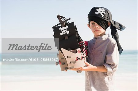 Boy in pirate costume playing with a toy boat Stock Photo - Premium Royalty-Free, Image code: 6108-05865967