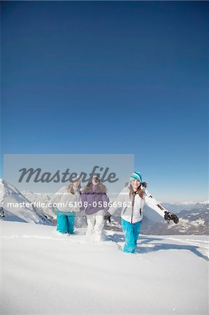 Three teenage girls in ski clothes, walking in snow Stock Photo - Premium Royalty-Free, Image code: 6108-05866962