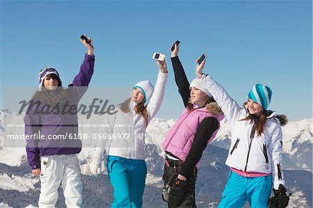 Four teenage girls in ski clothes, with their mobile phones in air Stock Photo - Premium Royalty-Free, Image code: 6108-05866977