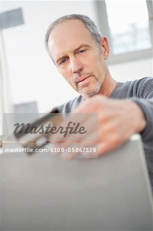Man doing online shopping with a laptop Stock Photo - Premium Royalty-Free, Image code: 6108-05867328