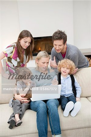 Family using a laptop Stock Photo - Premium Royalty-Free, Image code: 6108-05867372
