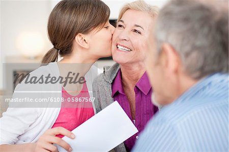 Girl kissing her grandmother with her grandfather sitting beside them Stock Photo - Premium Royalty-Free, Image code: 6108-05867567