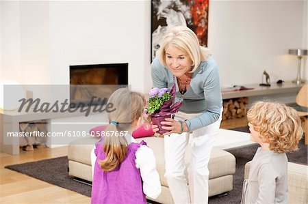 Woman giving a potted plant to her granddaughter Stock Photo - Premium Royalty-Free, Image code: 6108-05867667