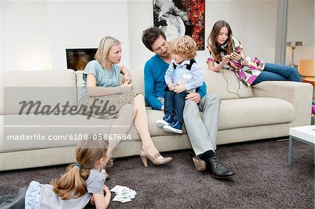 Family in a living room Stock Photo - Premium Royalty-Free, Image code: 6108-05867684