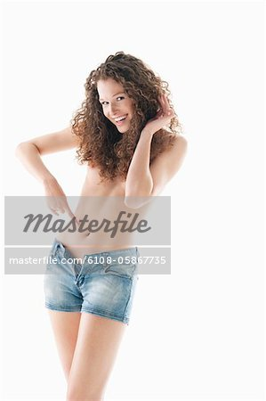 Woman pointing towards her abdomen and smiling Stock Photo - Premium Royalty-Free, Image code: 6108-05867735