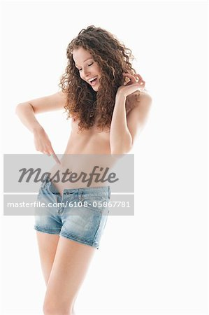 Woman pointing towards her abdomen and smiling Stock Photo - Premium Royalty-Free, Image code: 6108-05867781