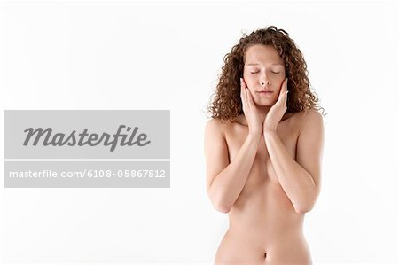 Close-up of a woman touching her cheeks Stock Photo - Premium Royalty-Free, Image code: 6108-05867812