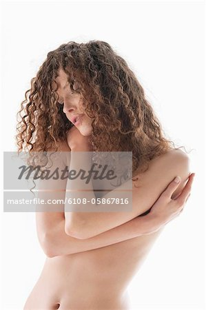 Woman covering her breasts Stock Photo - Premium Royalty-Free, Image code: 6108-05867816