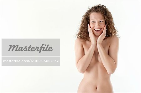 Close-up of a woman touching her cheeks and smiling Stock Photo - Premium Royalty-Free, Image code: 6108-05867837