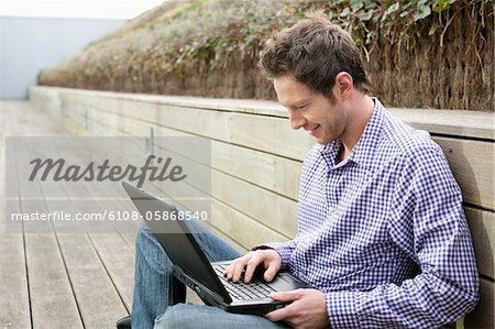 Man using a laptop on a boardwalk Stock Photo - Premium Royalty-Free, Image code: 6108-05868540