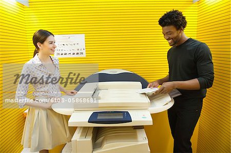 Business executives using photocopy machine in an office Stock Photo - Premium Royalty-Free, Image code: 6108-05868681