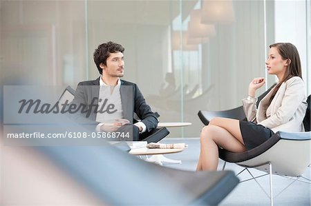 Business executives sitting on chairs in a waiting room Stock Photo - Premium Royalty-Free, Image code: 6108-05868744