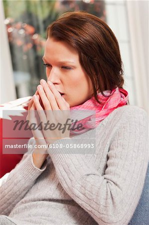 Young woman coughing Stock Photo - Premium Royalty-Free, Image code: 6108-05868993