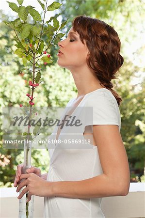 Young woman smelling plant Stock Photo - Premium Royalty-Free, Image code: 6108-05869118