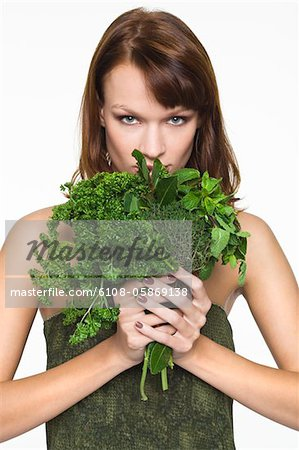 Young woman holding fresh herbs Stock Photo - Premium Royalty-Free, Image code: 6108-05869138