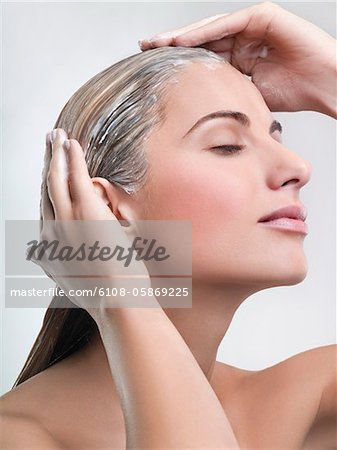 Young woman applying hair mask Stock Photo - Premium Royalty-Free, Image code: 6108-05869225