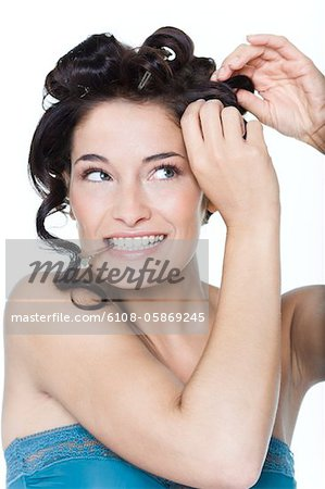Young woman fixing hair clips Stock Photo - Premium Royalty-Free, Image code: 6108-05869245
