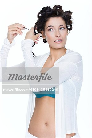 Young woman fixing hair clips Stock Photo - Premium Royalty-Free, Image code: 6108-05869249