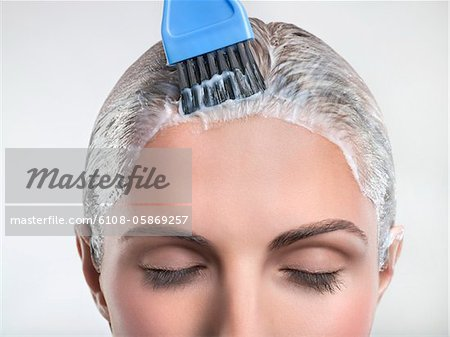 Young woman applying hair color Stock Photo - Premium Royalty-Free, Image code: 6108-05869257