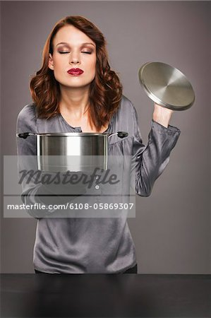 Young woman smelling aroma from stew pot Stock Photo - Premium Royalty-Free, Image code: 6108-05869307