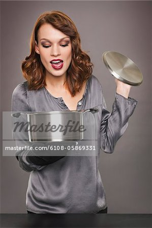 Young woman looking at content of stew pot Stock Photo - Premium Royalty-Free, Image code: 6108-05869331