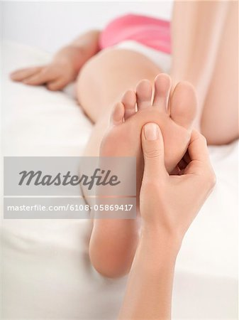 Woman receiving foot massage Stock Photo - Premium Royalty-Free, Image code: 6108-05869417