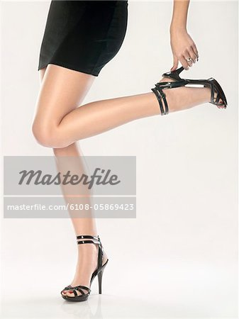 Woman putting on shoe Stock Photo - Premium Royalty-Free, Image code: 6108-05869423