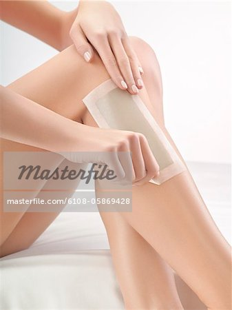 Woman waxing her leg Stock Photo - Premium Royalty-Free, Image code: 6108-05869428