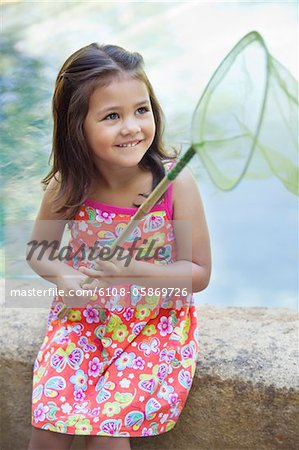 Little girl sitting by the swimming pool with net in hand Stock Photo - Premium Royalty-Free, Image code: 6108-05869726