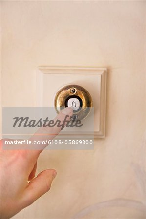 Close-up of a person's hand ringing door bell Stock Photo - Premium Royalty-Free, Image code: 6108-05869800
