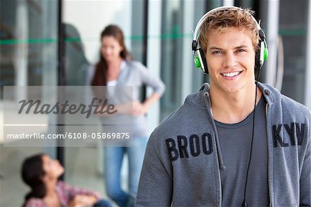Portrait of a man listening to music with headphones in a campus Stock Photo - Premium Royalty-Free, Image code: 6108-05869875