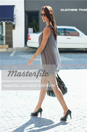 Side profile of a young woman walking Stock Photo - Premium Royalty-Free, Image code: 6108-05870035