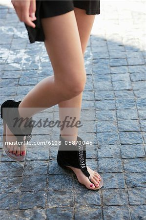 Low section view of a young woman wearing modern flat sandal Stock Photo - Premium Royalty-Free, Image code: 6108-05870045