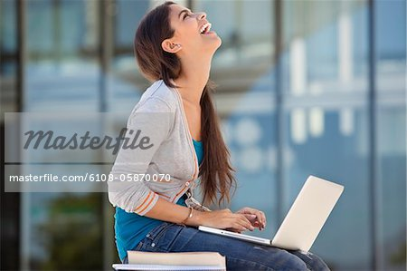 Woman laughing while using a laptop Stock Photo - Premium Royalty-Free, Image code: 6108-05870070
