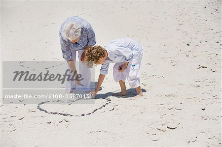 Senior woman and her grandson making a heart shape on the beach Stock Photo - Premium Royalty-Free, Image code: 6108-05870131