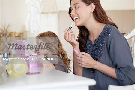 Young woman and little girl applying make-up at dressing table Stock Photo - Premium Royalty-Free, Image code: 6108-05870185
