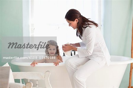 Woman giving a bath to her daughter Stock Photo - Premium Royalty-Free, Image code: 6108-05870188