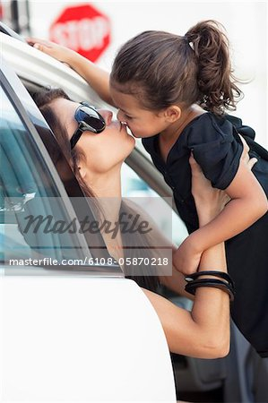 Beautiful young woman kissing her cute little daughter in a car Stock Photo - Premium Royalty-Free, Image code: 6108-05870218