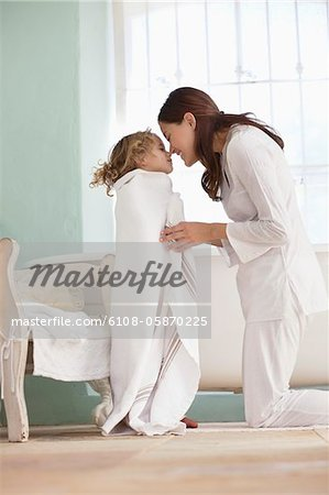 Woman rubbing noses with her daughter wrapped in towel after the bath Stock Photo - Premium Royalty-Free, Image code: 6108-05870225