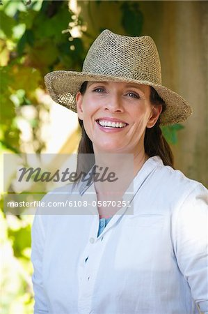 Portrait of a beautiful mature woman wearing hat and smiling Stock Photo - Premium Royalty-Free, Image code: 6108-05870251