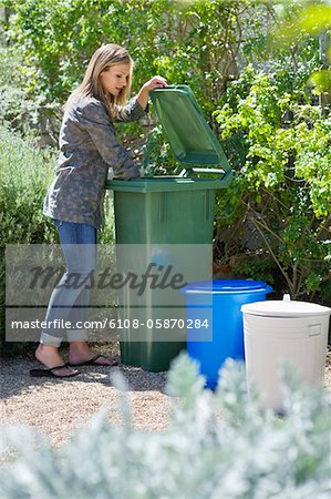 Woman looking into recycling bin Stock Photo - Premium Royalty-Free, Image code: 6108-05870284