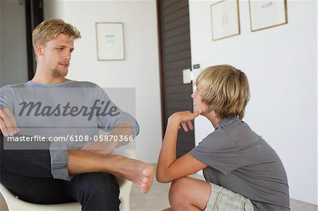 Young man talking to a teenage boy Stock Photo - Premium Royalty-Free, Image code: 6108-05870366