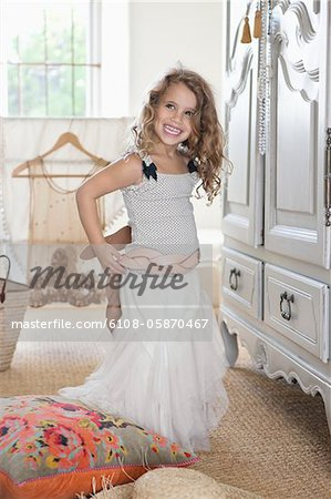 Cute little girl getting dressed like her mother in oversized clothes Stock Photo - Premium Royalty-Free, Image code: 6108-05870467